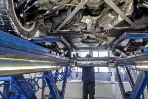 Révision voiture sur pont par un mécanicien